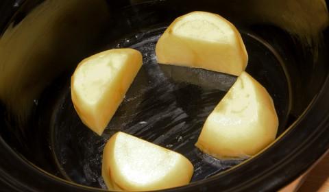 patata tagliata in 4 parti sul fondo della slow cooker